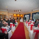wedding at Uphall Golf Club image of guests and bridal party with red carpet white covers on chairs with red bows